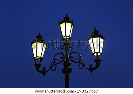 Vintage street light against the evening blue sky - stock photo