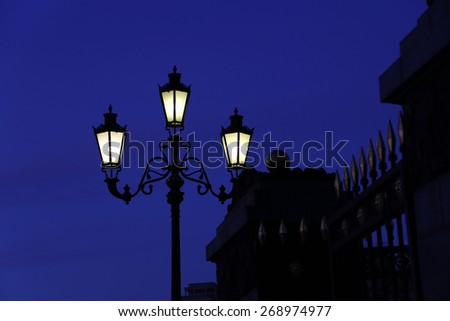 Vintage street light and gate against the night sky - stock photo