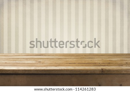 Vintage striped pattern wall and wooden deck tabletop - stock photo