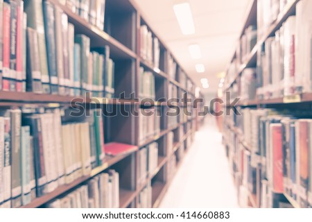 Vintage style blurred abstract background view of university student girl behind aisle of book shelves in school library: Blurry interior perspective indoor study room, table chair seat, book stack  - stock photo