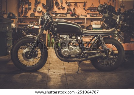 Vintage style cafe-racer motorcycle in customs garage  - stock photo