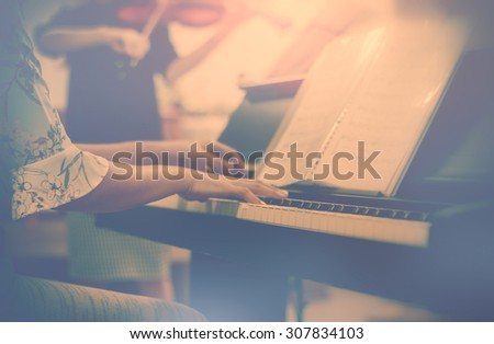 Vintage style Hands woman playing piano with light behind woman playing violin - stock photo
