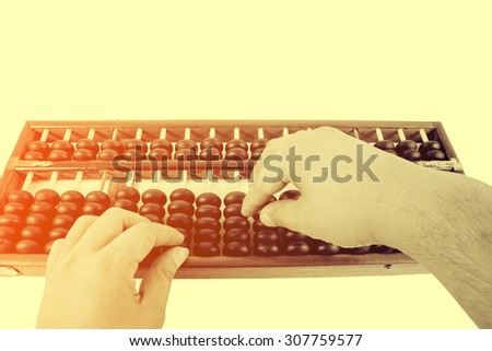 Vintage style - Human hand counting with wooden abacus beads. - stock photo