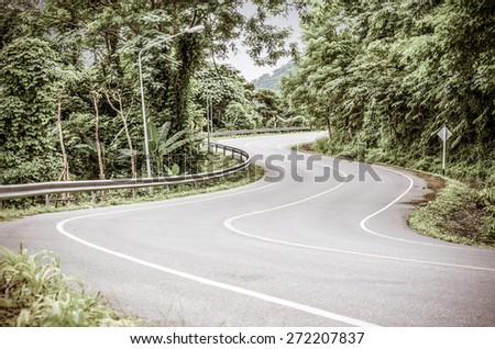 Vintage style image of a lonely snake curved road - stock photo