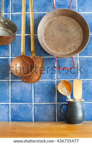 Vintage style kitchen accessories. Old utensils pan ladle pitcher with spoon, spatula. Wooden table and blue tile background. Kitchen interior concept.  - stock photo