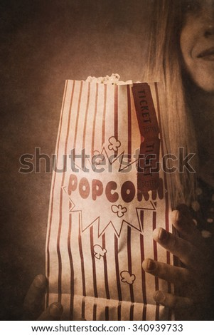 Vintage style movie poster of a old fashioned girl holding cinema popcorn at nostalgic retro theater. Classic hollywood flicks - stock photo