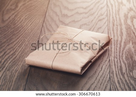 vintage style parcel wrapped with rope, toned photo - stock photo