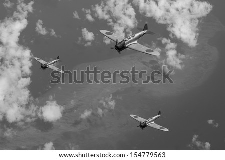 Vintage 'style' photo depicting Japanese WWII aircraft flying over a coral reef in the Pacific Ocean, circa 1942. (Artist's Impression/recreation) - stock photo