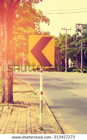 Vintage style photo of the turning left road sign on roadside. - stock photo