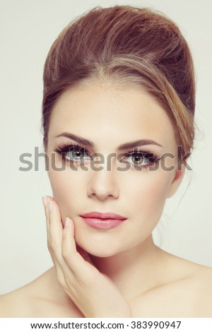 Vintage style portrait of young beautiful stylish girl with hair bun and winged eyes make-up - stock photo