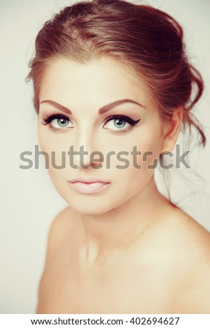Vintage style portrait of young beautiful woman with eyebrows tattoo and hair bun, selective focus - stock photo