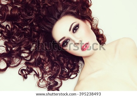 Vintage style portrait of young beautiful woman with fresh make-up and long curly hair - stock photo