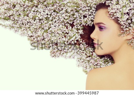 Vintage style profile portrait of young beautiful girl with bright make-up and lilac in her long hair - stock photo