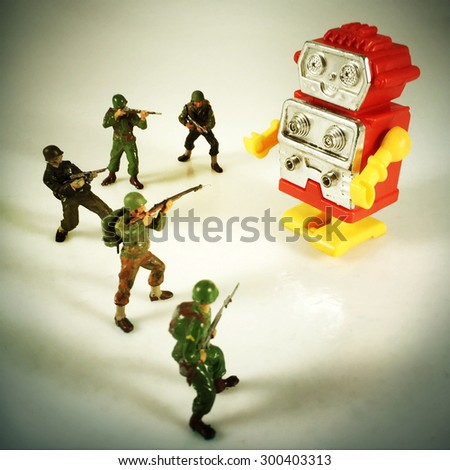 Vintage style Toy Soldiers shooting at robot with an Instagram style filter - stock photo