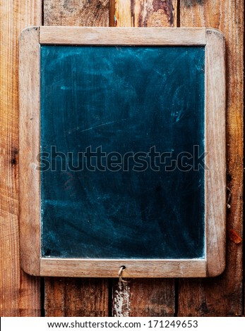 Vintage style wood framed chalkboard over old wood background. Space for insertion of your own text. - stock photo