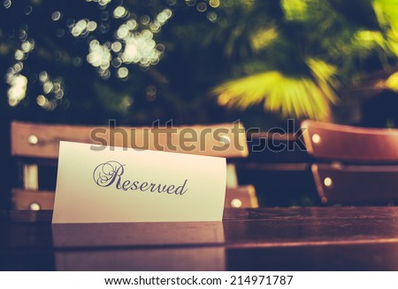 Vintage Styled Image Of A Reserved Sign On A Table At An Outdoor Restaurant - stock photo