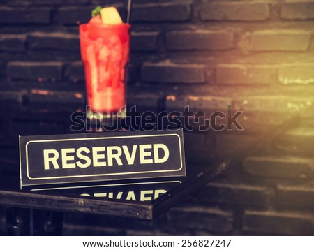 Vintage styled image of a reserved sign on a table in restaurant. - stock photo