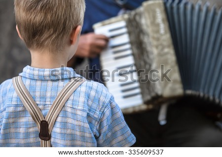 Vintage styled little boy with suspenders listen carefully to a street musician playing an accordion/Childhood Street Music Concert - stock photo