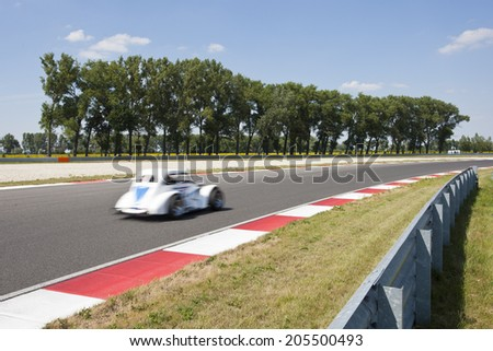 Vintage styled race car driving through the apex of a race track past the red and white curb stones - stock photo