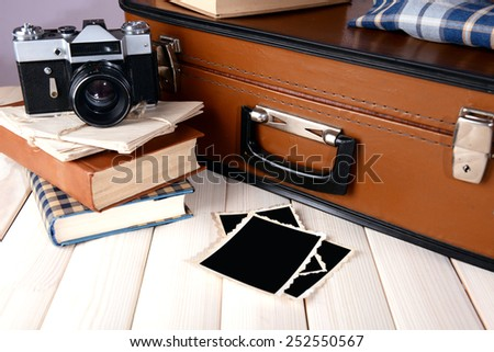 Vintage suitcase with clothes and books on table on dark background - stock photo