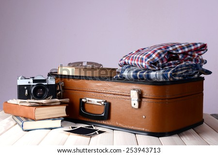 Vintage suitcase with clothes and books on table on dark colorful background - stock photo
