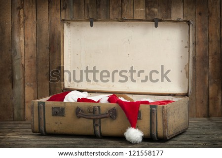 vintage suitcase with santa clothes, on an old wooden floor - stock photo