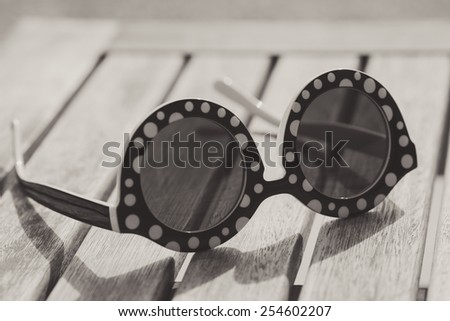 Vintage sun glasses on a table in summer - stock photo