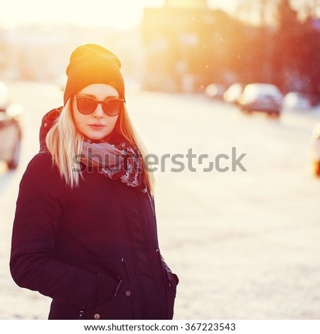 vintage sunny portrait of cute young blond girl with heat scarf and black sunglasses on bright natural city street background. Outdoor winter photo - stock photo