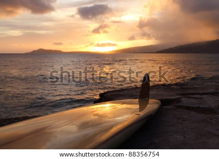 Vintage surfboard on rocky shoreline framed by the southern Oahu coast in Hawaii. - stock photo