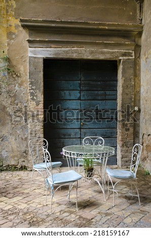 Vintage table and chair in the yard of an old house - stock photo