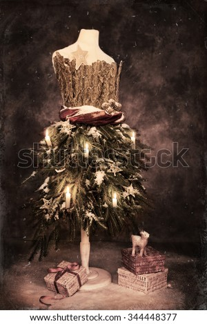 Vintage tailors dummy dressed for a festive Christmas with gifts  - stock photo