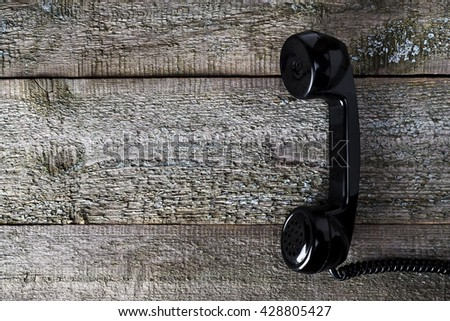Vintage telephone handset. Old black nostalgic phone on brown vintage background for concepts. Retro handset lie on wooden texture table backdrop - stock photo