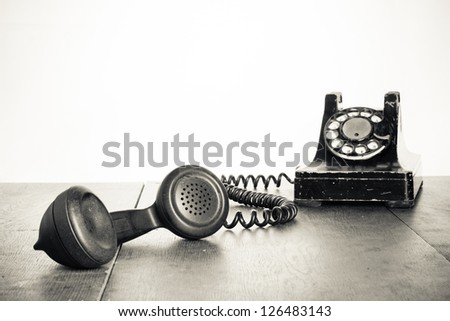 Vintage telephone handset on old table sepia photo - stock photo