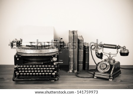 Vintage telephone, old typewriter, books on table desaturated photo - stock photo