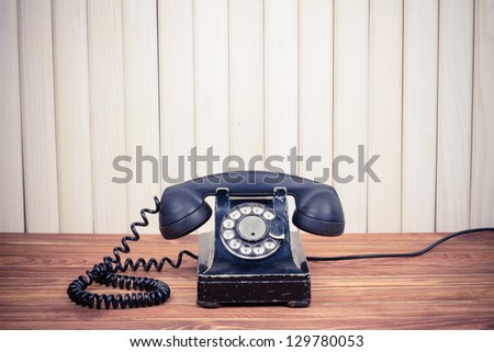 Vintage telephone on old table near wood wall - stock photo