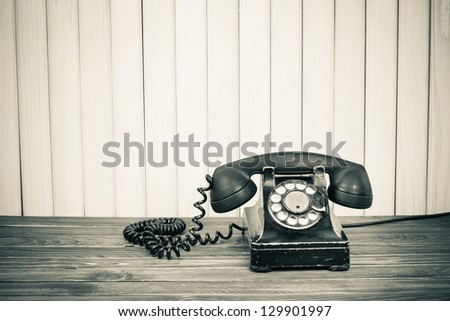 Vintage telephone on old table sepia photo - stock photo