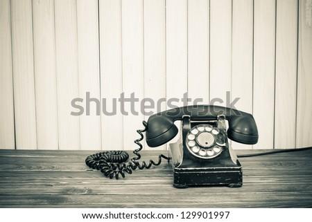 Vintage telephone on old table sepia photo - stock photo
