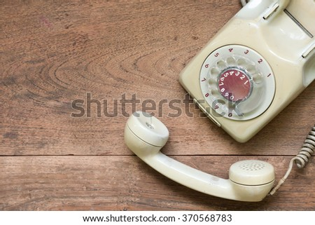 vintage telephone on wooden table background. - stock photo