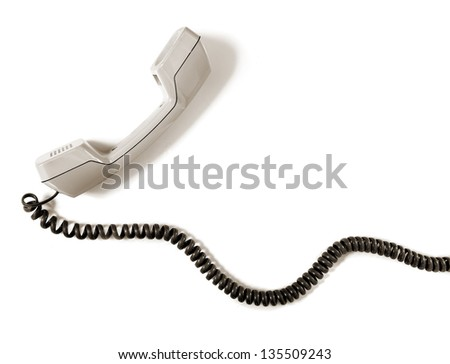 Vintage telephone receiver with cable over white - stock photo