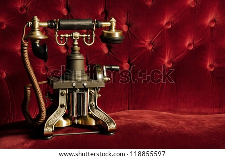 Vintage Telephone - Retro Phone on Classic Red Velvet Couch - stock photo