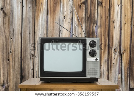 Vintage television on table with rustic wood wall.   - stock photo