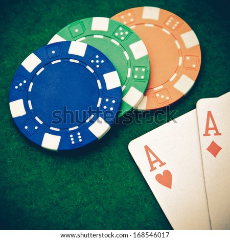 Vintage - Texas holdem pocket aces on casino table with copy space and chips - stock photo