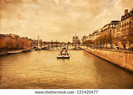 vintage textured picture of the river Seine in Paris with a tourist boat and the Notre Dame Cathedral in the background - stock photo
