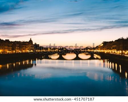Vintage themes of a Ponte Santa Trinita (Holy Trinity Bridge) over River Arno, View of after sunset down at Ponte Santa Trinita- Florence, Tuscany, Italy-filter image - stock photo