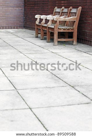 Vintage timber bench on a concrete walkway against a brickwall. - stock photo