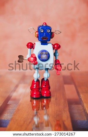 Vintage tin robot over a wood table with reflection. - stock photo
