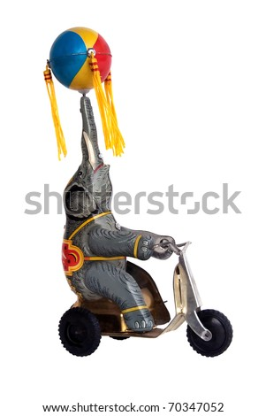 Vintage tin wind-up toy, elephant on tricycle with ball - stock photo