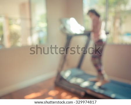 vintage tone blur image of Cute girl running treadmill on day time for background usage. - stock photo