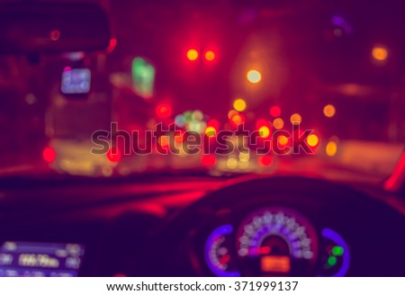 vintage tone blur image of inside cars with bokeh lights with traffic jam on night time for background usage. - stock photo