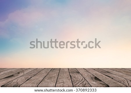 vintage tone color blue sky and clouds background with sunny flare light with aged wood panel perspective:retro wood floorboard line with blur pastel atmosphere backdrop:advertising product on display - stock photo